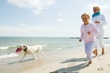 Family with dog playing at the beach