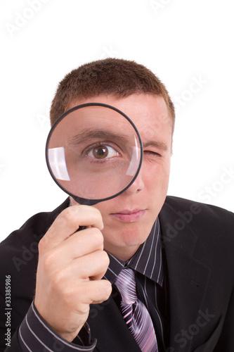Close-up man looking through magnifying glass