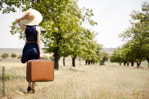 Lonely girl with suitcase at countryside.
