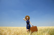 Redhead girl with suitcase at spring wheat field.