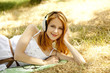 Beautiful redhead girl with headphones at garden.