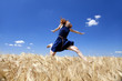 Redhead girl at wheat field in summer day.