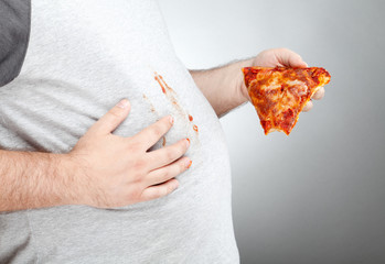 Fat man wiping pizza sauce on his shirt