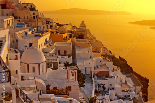 Sunset at Santorini island , Greek church with a cross