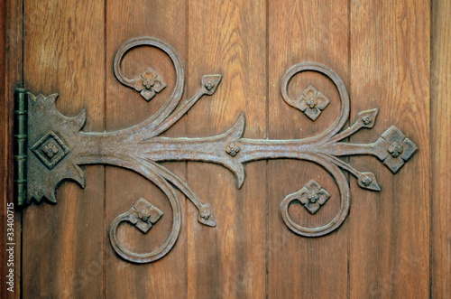 Close-up Of An Ornamental Iron Hinge On An Old Wooden Door