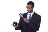 Man examining piggy bank with a magnifying glass