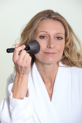 Woman in bathrobe using blusher brush