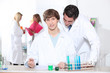 Teacher checking students work in laboratory