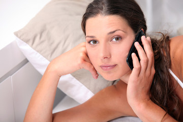 woman answering her phone in her bed