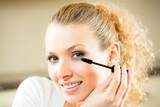 Young woman applying mascara with lash brush at home poster