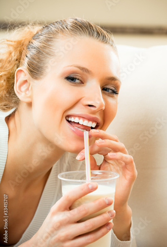 Young happy smiling woman drinking milk at home