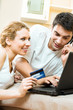 Couple with laptop, paying by credit card in internet store