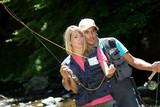 Couple flyfishing in river during summer vacation