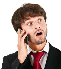 Businessman surprised while talking at the phone