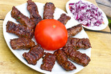 Traditional Croatian cevapcici with red onion and tomato
