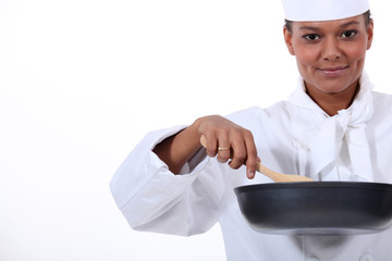 female cook with a high-sided frying pan and a wooden spoon