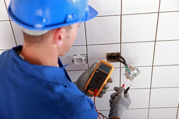 Electrician checking the wiring of a wall socket