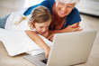 Adorable girl using laptop with grandmother