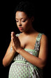 Young pregnant woman praying