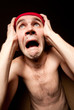 Terrified screaming man holding his head