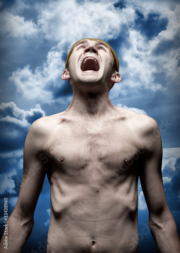 Despaired screaming man against dramatic sky