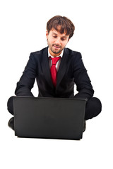 Businessman sitting on the floor while using his laptop