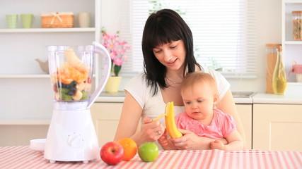 Mother and her baby daughter preparing a milkshake
