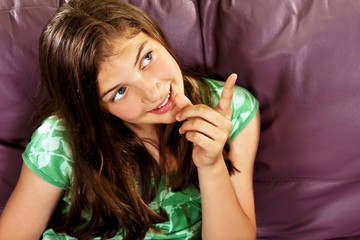 Teenage girl sitting on the sofa pointing with finger