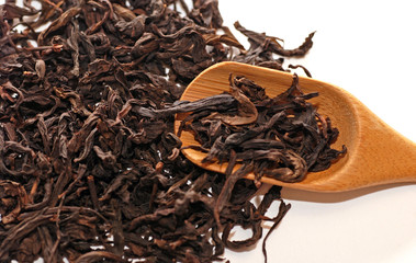 Dried chinese black tea leaves with teaspoon.