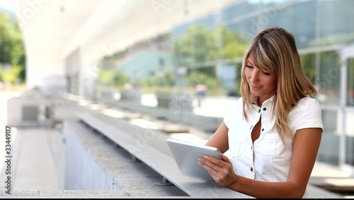 Blond woman using electronic tablet in town