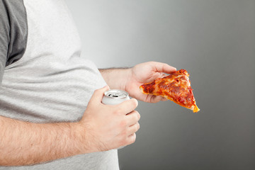 Man holding pizza slice and canned beverage
