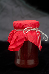 Glass pot with strawberry jam against black background