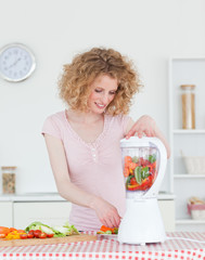 Attractive blonde woman using a mixer in the kitchen