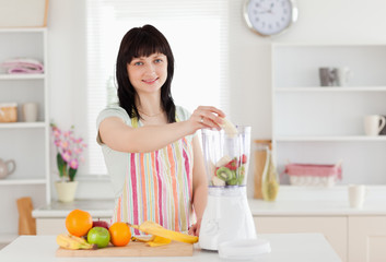 Cute brunette woman putting vegetables in a mixer while standing