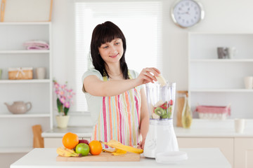 Gorgeous brunette woman putting vegetables in a mixer while stan