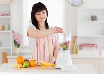 Lovely brunette woman putting vegetables in a mixer while standi
