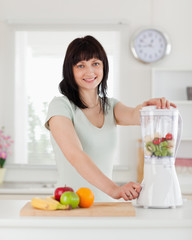 Good looking brunette female using a mixer while standing