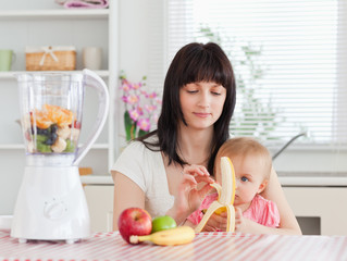 Cute brunette woman pealing a banana while holding her baby on h