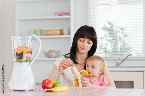Attractive brunette woman pealing a banana while holding her bab