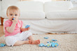 Cute baby playing with puzzle pieces while sitting on a carpet