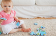 Lovely baby playing with puzzle pieces while sitting on a carpet