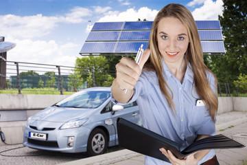 Junges Mädchen zeigt den Daumen nach oben vor einem Elektroauto