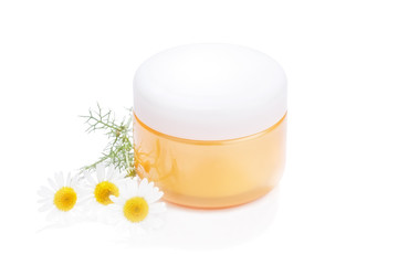 Jar of moisturizing cosmetics with camomile flower