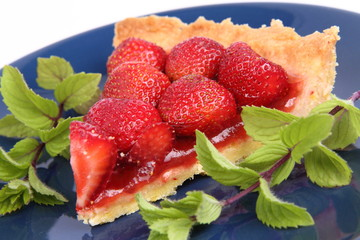 Piece of Strawberry Tart decorated with mint twigs
