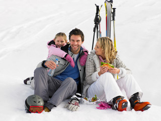 Young Family With Picnic On Ski Vacation