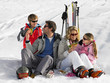Young Family Sharing A Picnic On Ski Vacation