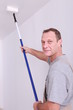 Decorator using a long roller to paint a ceiling