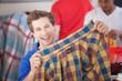 Grinning Man Holding Shirt