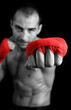 Young Boxer fighter over over black background. Focus on hand.