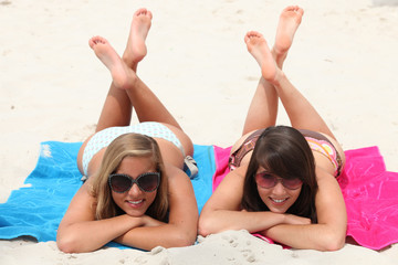 two girls lying on their stomachs with legs crossed